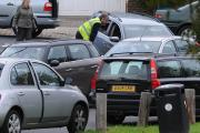 A parking enforcement officer speaks to a driver outside Westdene School in Brighton