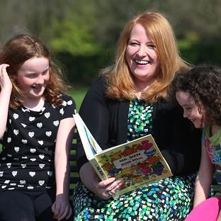 Alliance candidate Naomi Long chats with Emma, left, and Jessica Cochrane at a children's book reading event