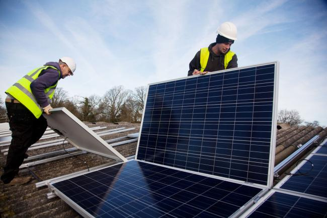 Andy Tyrrell and Jake Beautyman installing solar panels on a barn roof at Grange farm, near Balcombe