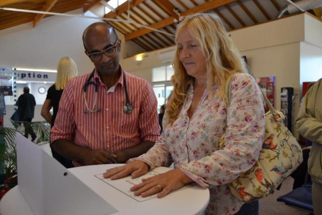 Dr Madhava Dissanayake watches hospital visitor Christine Iverson as she takes the test