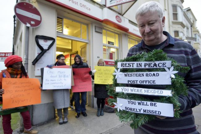 Paul Sweetman of City Books laying a wreath with mourners outside the Western Road Post Office on its last day before closure in February.