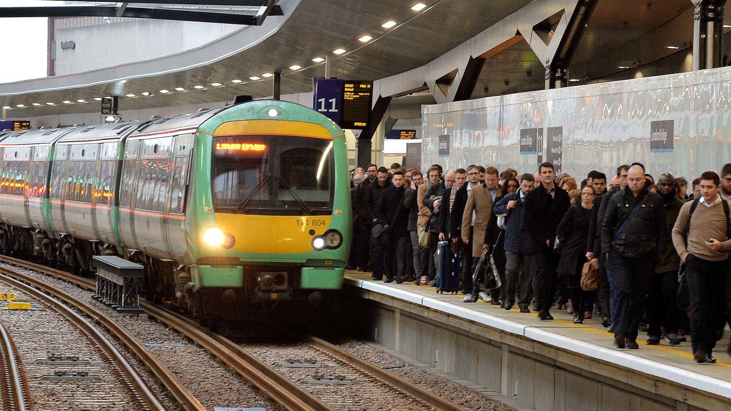 Commuters at London Bridge railway station as a Southern train pulls in