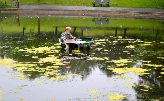 Volunteer sets up desk in pond so park cleaning session can