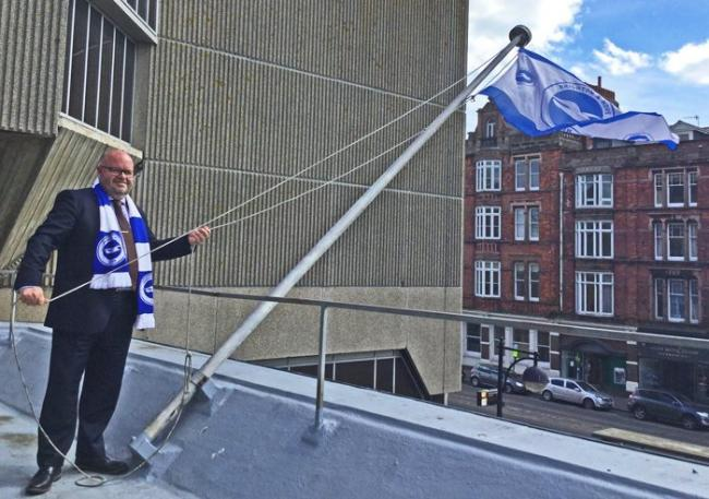 Warren Morgan hoists the Albion flag at Hove Town Hall