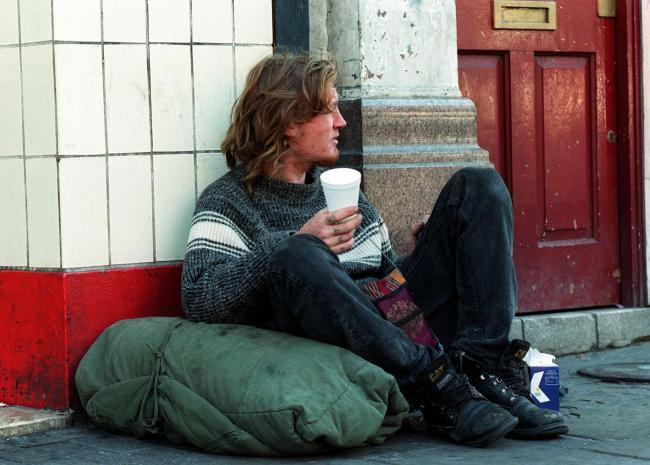 A homeless man sitting beside a doorway begs for money from passers-by