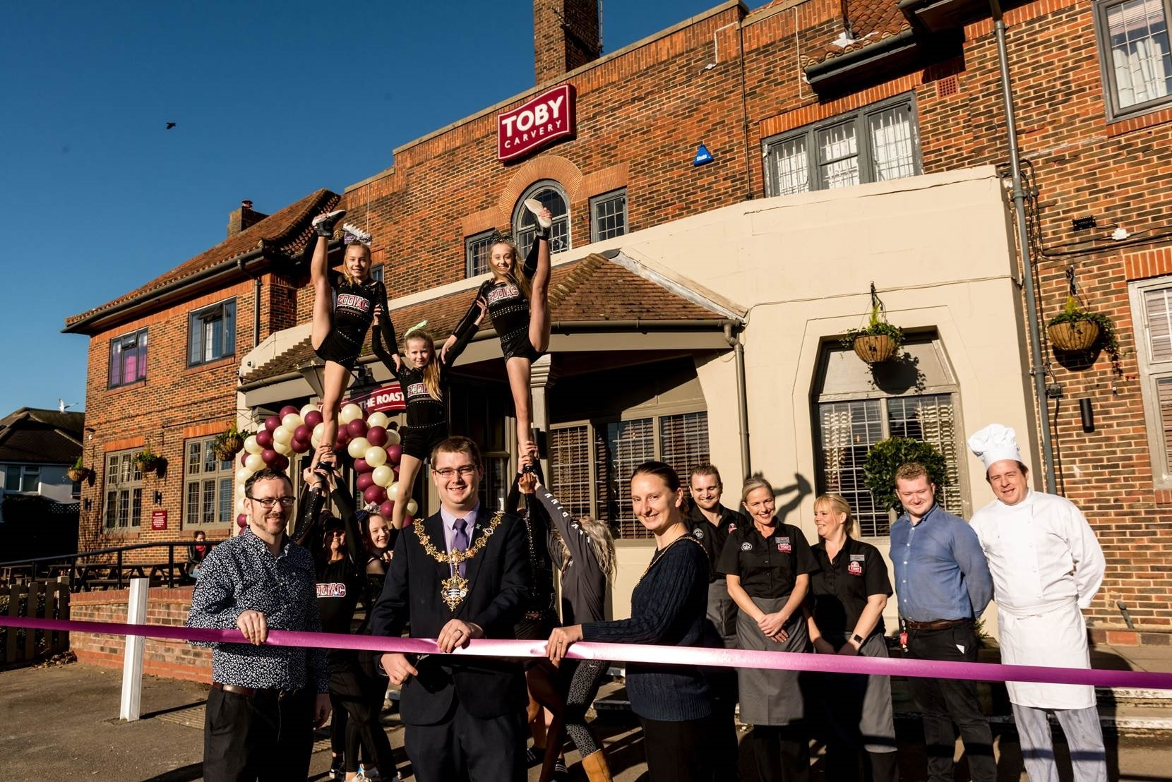The Mayor and Mayoress of Worthing, Alex and Fran Harman (centre), cut the ribbon and reopen the new look Toby Carvery Downlands with the help of the Toby staff and the Zodiac cheerleading group