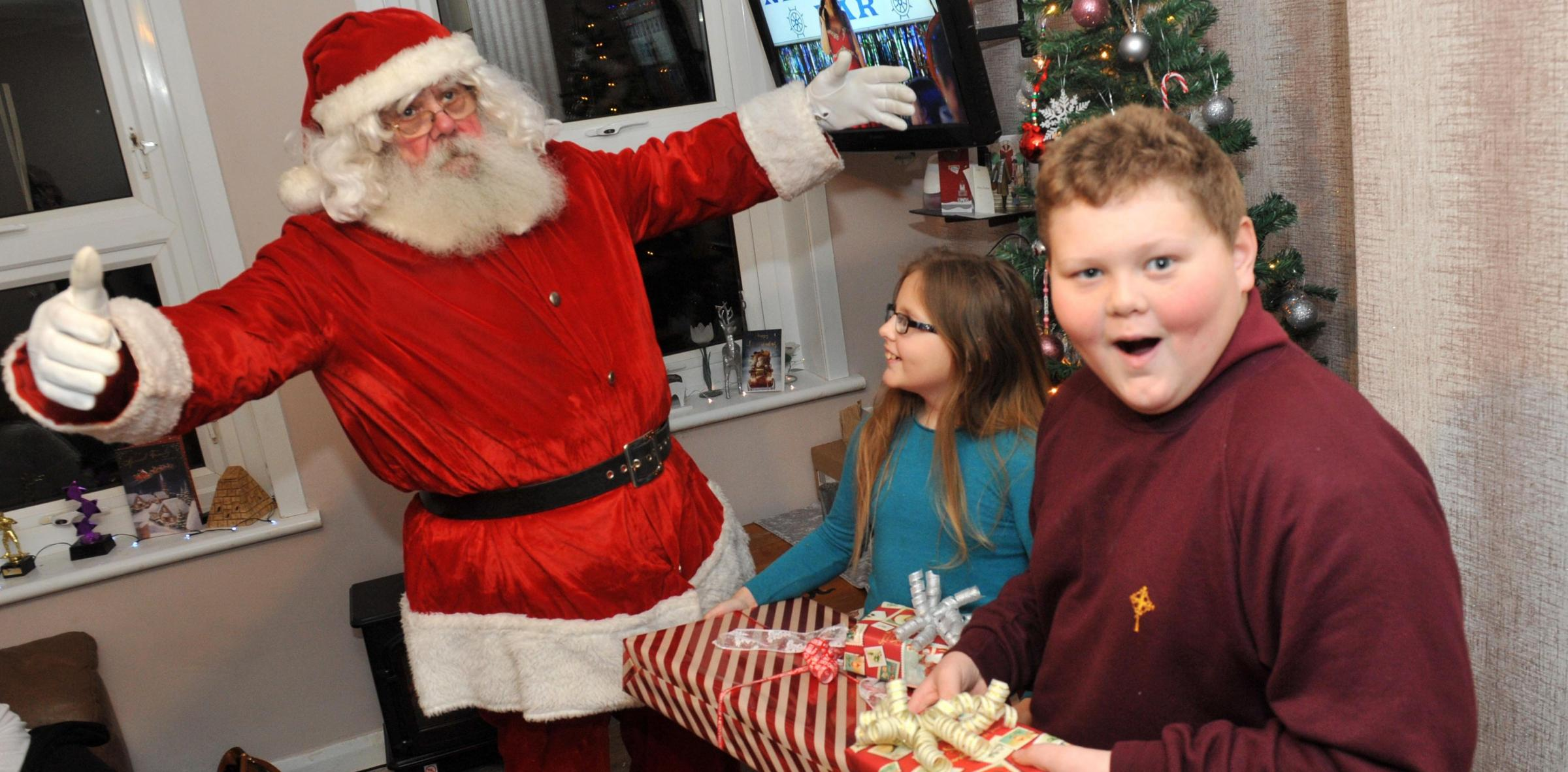 Father Christmas gives presents to Caitlin Reeves, ten, and her brother Peter Reeves, 11