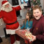 The Argus: Father Christmas gives presents to Caitlin Reeves, ten, and her brother Peter Reeves, 11