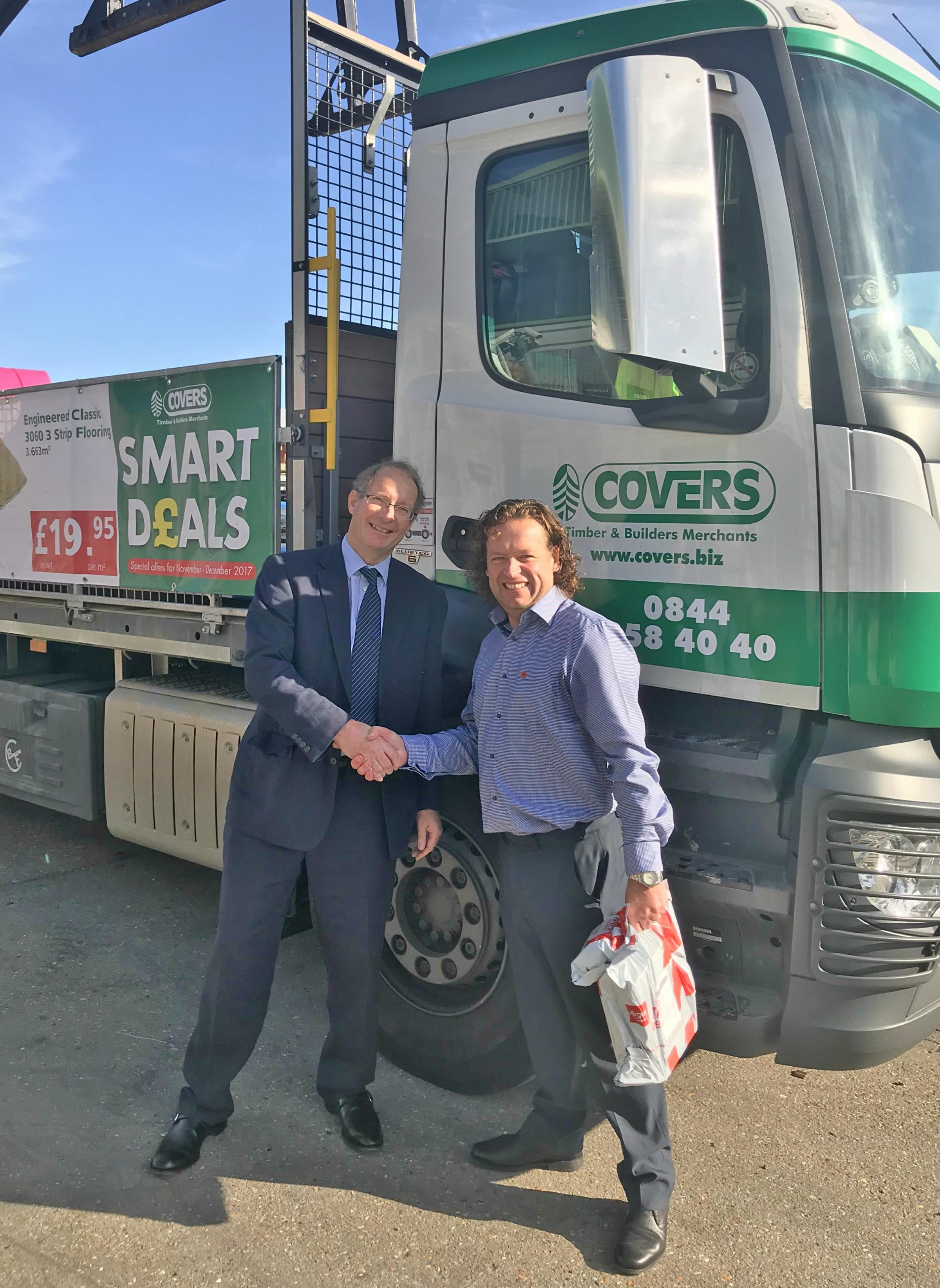 Rupert Green, Chairman at Covers Timber & Builders Merchant, congratulating Nick Terry, Sales Representative at Covers of Brighton, on his long service.