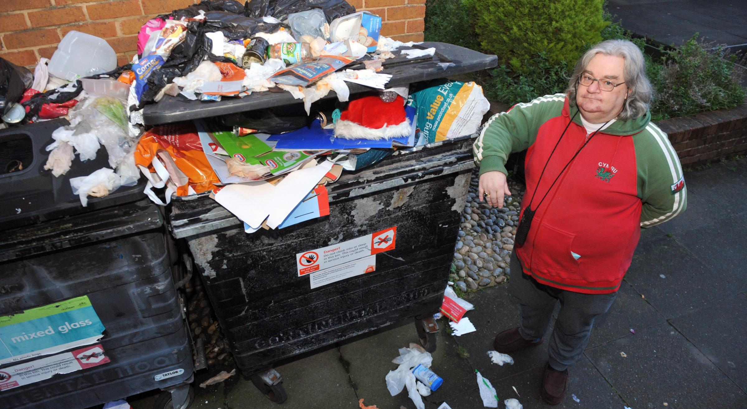 Owen Spence with the mountain of rubbish outside his apartment block on New England Street Photo by Allan Hutchings