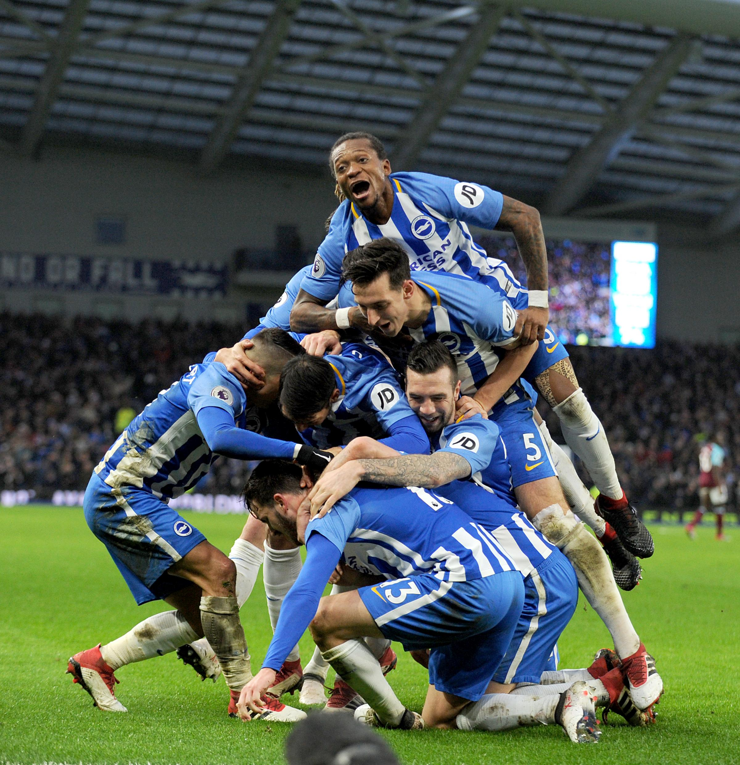 The Albion players engulf Pascal Gross after his clincher against West Ham