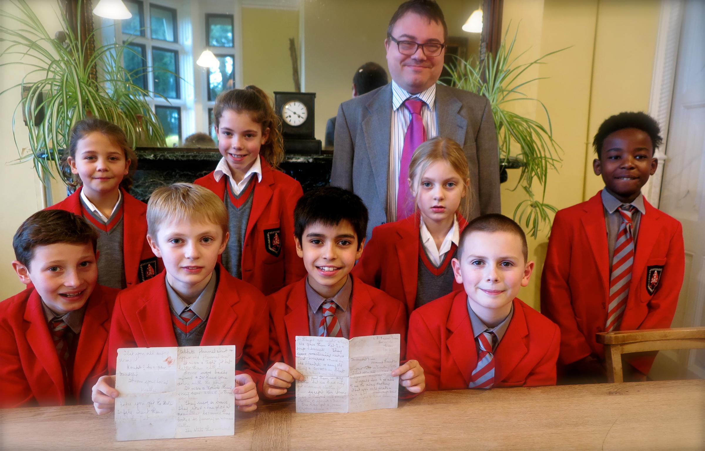 Sompting Abbotts Headmaster Stuart Douch and pupils display the letter hidden under floorboards for almost 80 years