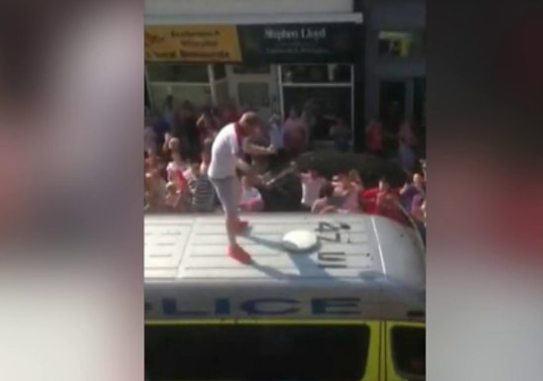 An over-excited England fan celebrates on the roof of a police van in Eastbourne