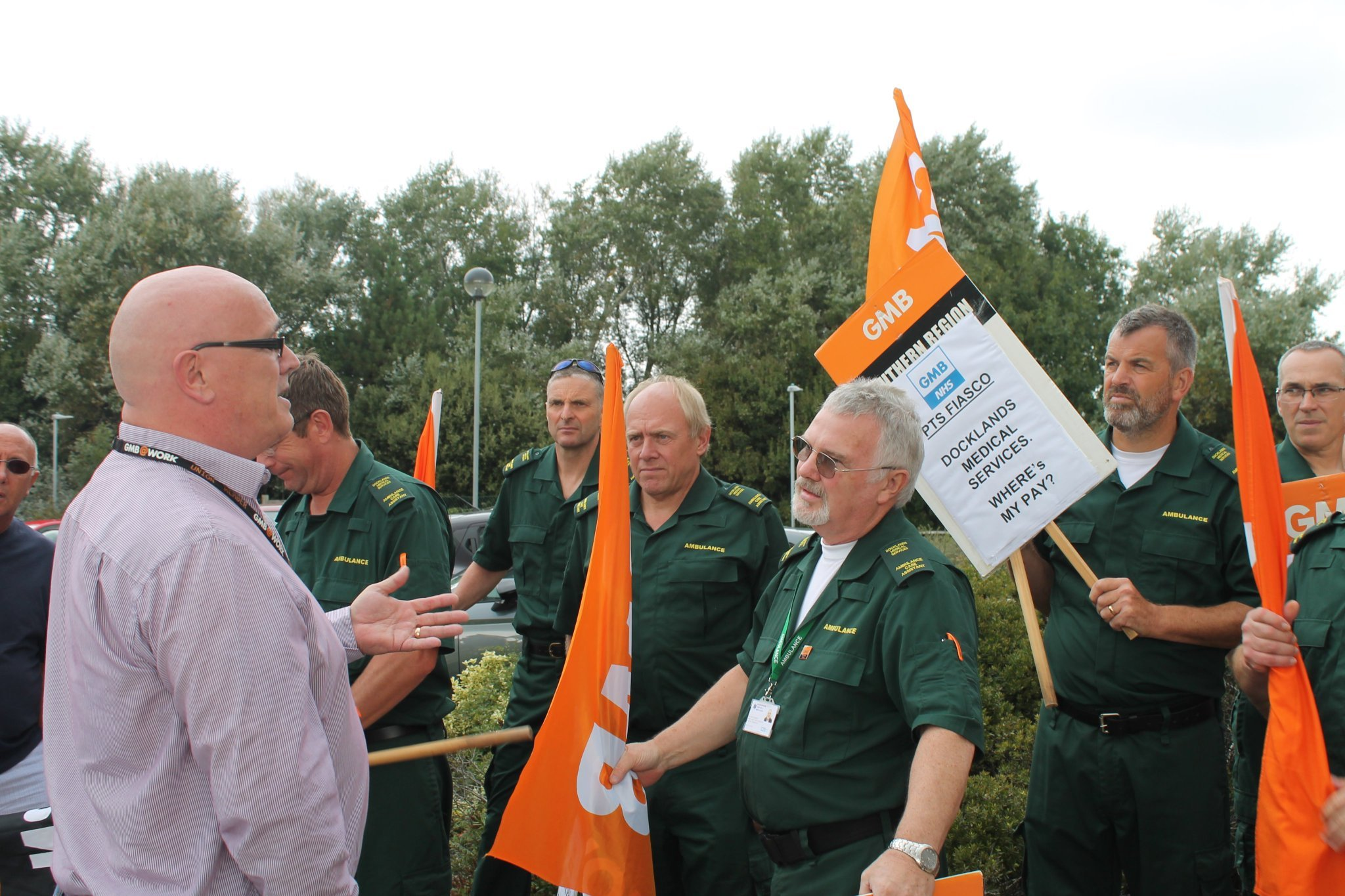 Ambulance staff marching in protest, with a GMB organiser