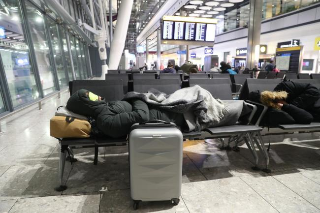 Passengers sleeping in the arrivals hall at Heathrow airport after departures were temporarily suspended last night following reports of a drone at the airport. PRESS ASSOCIATION Photo. Picture date: Wednesday January 9, 2019. See PA story AIR Drone. Phot