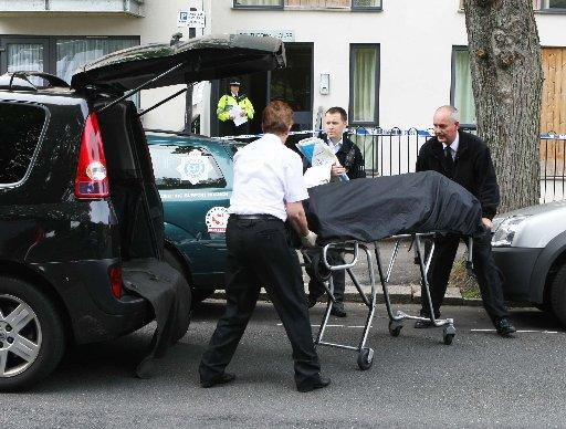 TRAGEDY: One of the bodies is removed from the Hove property where the Sudanese couple lived