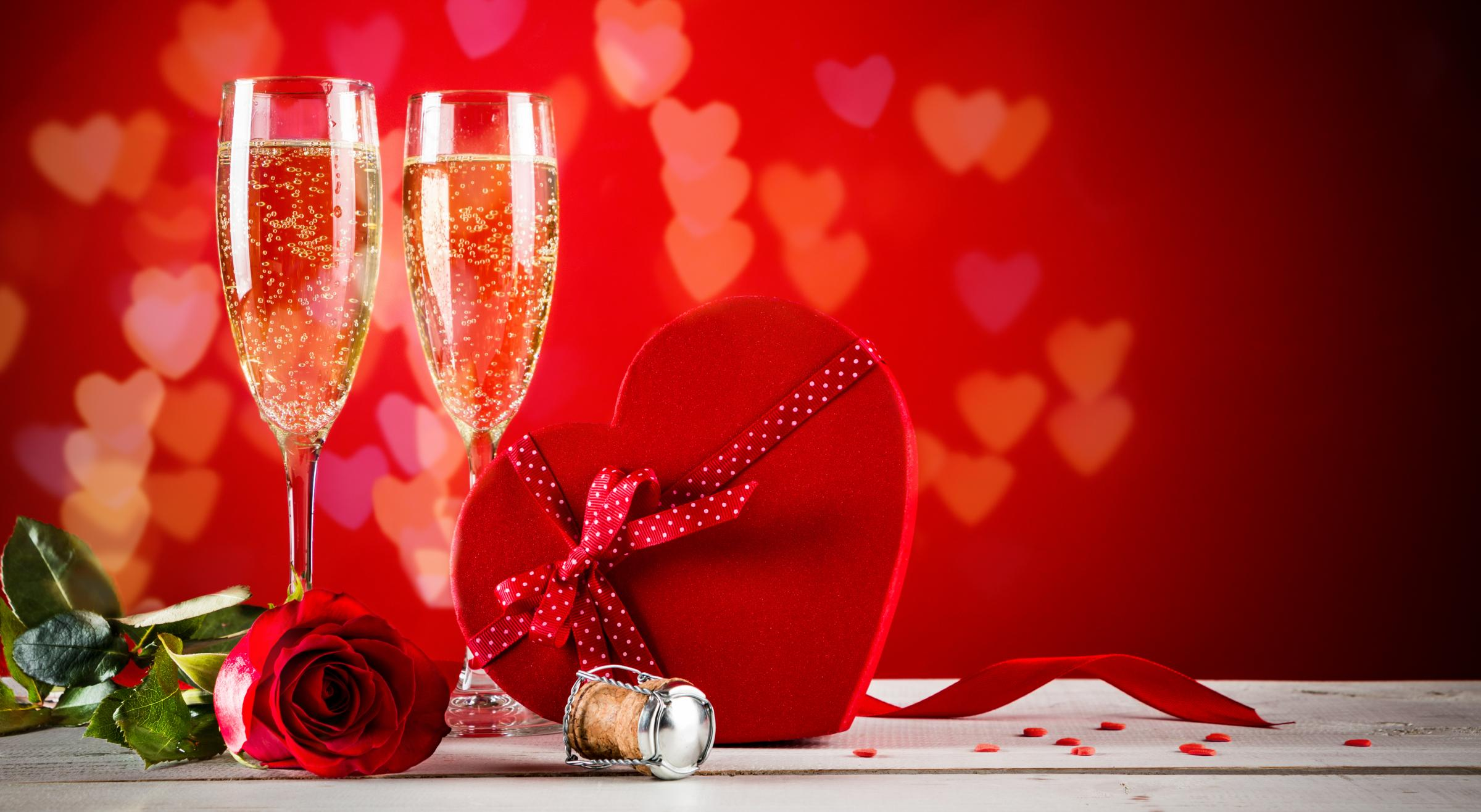 Background of Valentines day celebration with champagne, rose, heart shaped present and red candies..