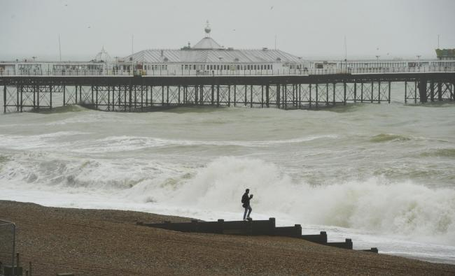 Brighton UK 3rd March 2019 -  A visitor gets a close look at the sea in Brighton as Storm Freya batters parts of Britain today.