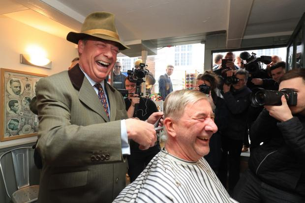 The Argus: Nigel Farage cuts a man's hair in East Street Barber's in Shoreham