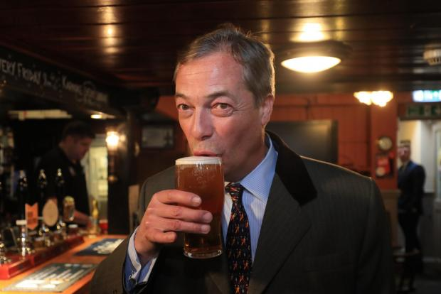 The Argus: Nigel Farage sips a pint of Ale in The Marlipins pub in Shoreham