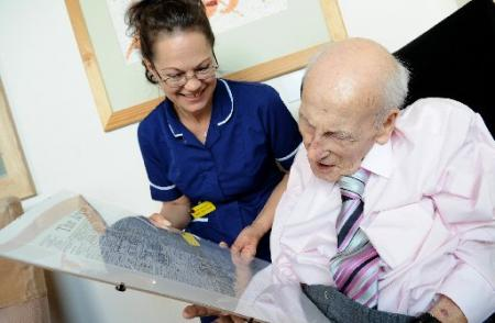 Henry Allingham with Julie Millward, Senior Staff Nurse as she reads a copy of The Argus published on Mr Allingham's birthday.
