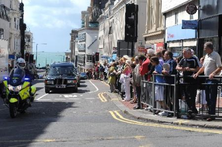 Crowds in West Street line up as the funeral cars go past.